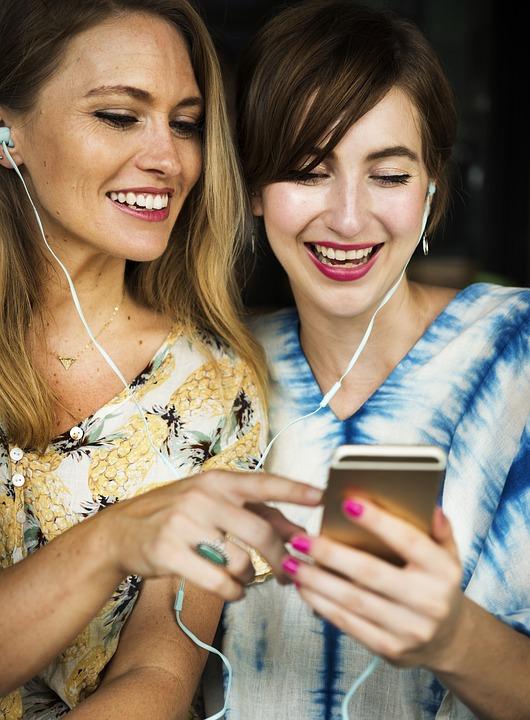 Kobiety na swoim smartfonie wyszukują ciekawych ofert SPA